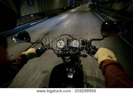 Soft focus shot with motion blur of motorcycle driver riding through dark dangerous tunnel on vehicle wears protection helmet and leather gloves