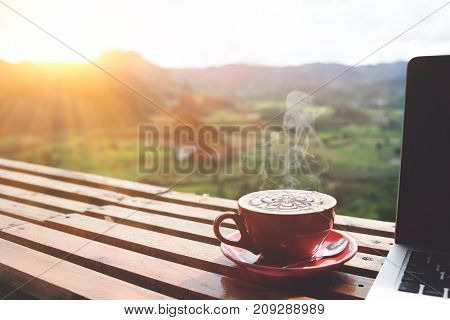 Coffee morning and laptop on wooden table with beautiful mountain background. Worklife balance concept