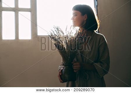 Attractive sensual woman in natural cotton linen robe holds bouquet of dry fresh lavender in room decorating florist professional