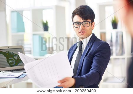 Young economist with papers looking at co-worker during conversation