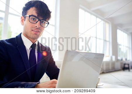 Young salesman looking at camera while analyzing online data