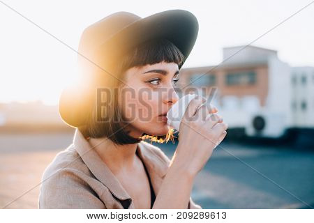 Attractive adorable woman with natural makeup sips on coffee in early morning on sunrise or sunset with light leaks from to go cup wears hipster fedora hat