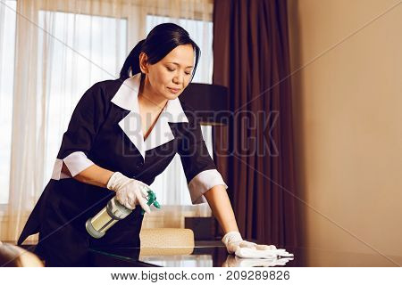 Let me clean it. Competent maid bowing head while looking downwards and preparing room for new guest