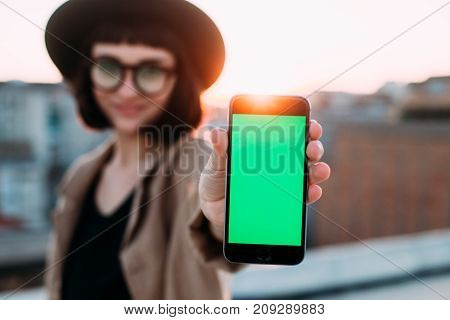 Adorable cute and pretty young woman in hipster millennial trendy outfit shows smartphone with chroma key for own image to camera smiles on rooftop with amazing sunset