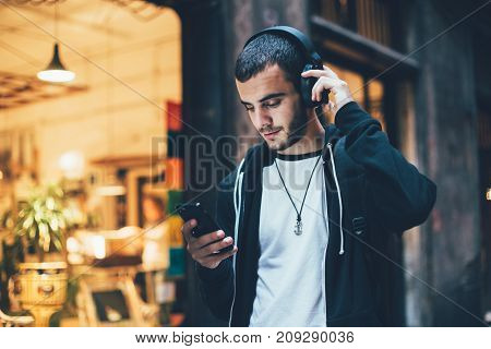 Hispanic young attractive man stands in dark street in front of shop changes songs and tracks on smartphone listens to music in wireless headphones. Hipster with slight beard