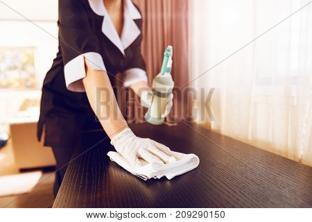 With care. Professional maid holding cleaning liquid in left hand and standing close to chest of drawers while polishing it