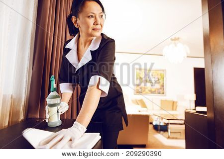 Deep in thoughts. Delighted female person holding bottle with cleaning liquid and leaning on table while looking aside