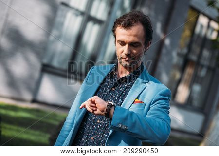 handsome stylish middle aged man man checking wristwatch outside