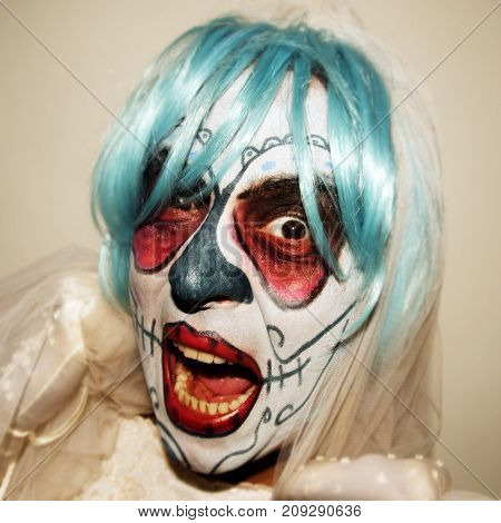 closeup of a scary bride with a mexican calaveras makeup, short blue hair and veil