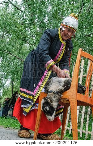 Tyumen, Russia - June 2, 2007: Holiday of nationalities. Nenets woman processes cervine skin in cultural center of North people. Nenets - aboriginals of Russian North