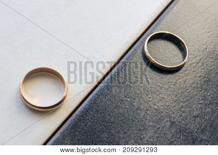 Two separate wedding rings on a black and white background. Concept - differences opposites and separation.