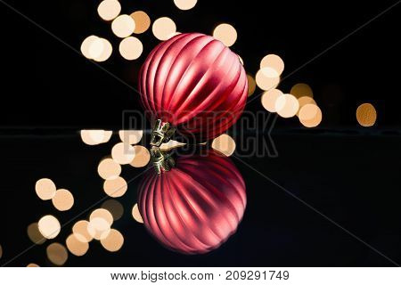 Red holiday ornament refected on glass surface soft Christmas lights. Dark black background isolated color.