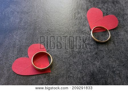 Wedding rings and red heart. Black background. The concept of divorce parting infidelity .