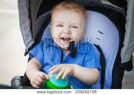 happy boy blonde boy sitting in pram, joy child playing with his cup in pram