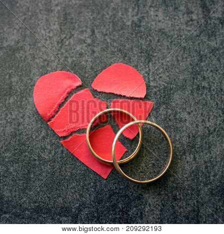 Wedding rings and broken red heart. Black background. The concept of divorce parting infidelity .