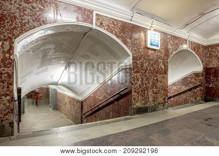 Brown tunnel with pathway go down to metro station at Moscow, Landscape of sidewalk with stair banisters and curve arch in underground at Russia