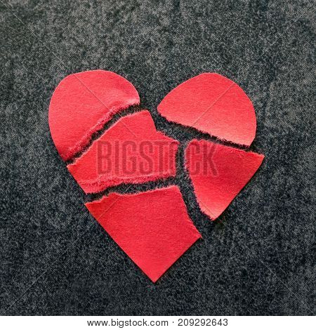 Torn red paper heart. Black background. The concept of divorce parting separation.