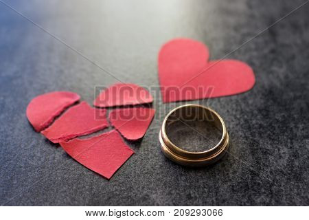 Wedding rings and broken red heart. Black background. The concept of divorce parting infidelity .Selective focus.