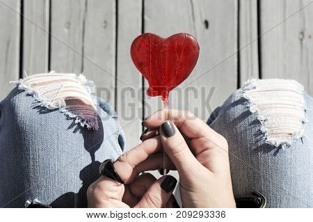 Red heart shaped lollipop in a trendy fashionable woman's hands, top view.