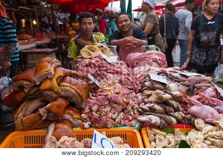 BANGKOK, THAILAND, JANUARY 05, 2017 : Men selling meat and offals in the Khlong Toei market in Bangkok, Thailand