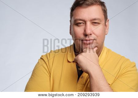 Fat man in yellow t-shirt dreams about something and looking at the camera languidly.