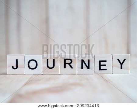 Word spell Journey by wooden tile font on blur wood background