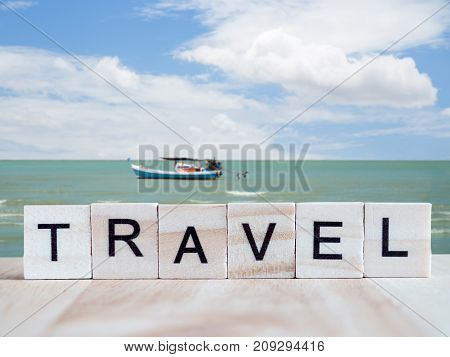 Word spell Travel by wooden tile font on blur seascape background