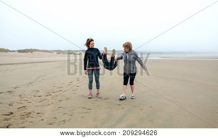 Three generations female walking on the beach in autumn