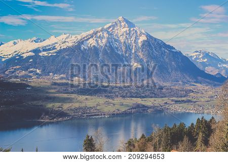 View of highest summit Burgfeldstand mountain of Emmental Alps covered in snow with clear lake reflect hills and green meadow with trees in winter under blue sky in Bernese Oberland at Switzerland