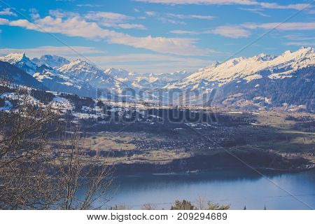 Large hill of Emmental Alps and lake in winter, Panorama view of Burgfeldstand mountain range covered by snow with blue lagoon reflection clear sky surrounding by meadow and green pine Christmas tree in Bernese Oberland at Switzerland