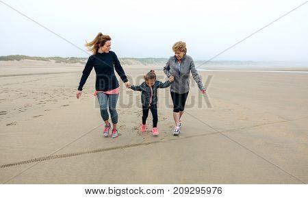 Three generations female running on the beach in autumn