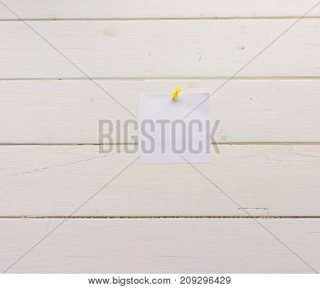 White square sheet of paper pinned to wooden boards. White-painted surface in a rustic style. Close-up. The top view. Background with copy space