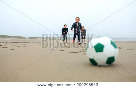 Soccer ball with three people running in the background