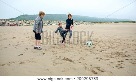 Three generations female playing soccer on the beach in autumn