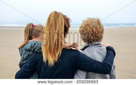 Back view of three generations female looking at sea on the beach in autumn