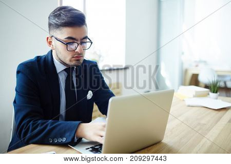 Young manager concentrating on networking and learning online data