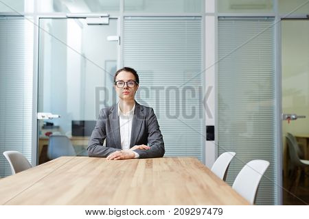 Serious employer waiting for another applicant by table in boardroom