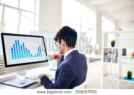 Businessman drinking tea while sitting in front of computer monitor in office