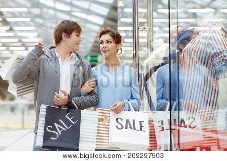 Young affectionate couple with paperbags discussing new purchase while walking along window display of clothing department