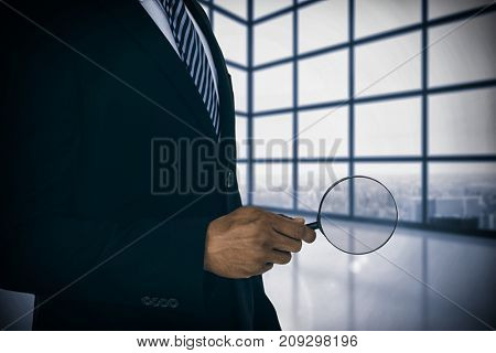 Mid section of businessman holding magnifying glass against room with large window showing city