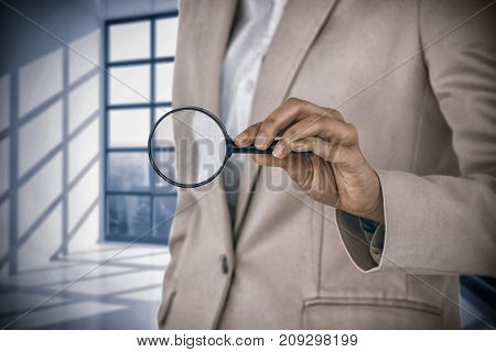 Mid section of businesswoman holding magnifying glass against room with large window showing city