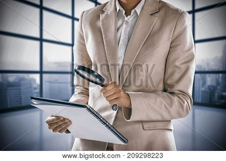 Businesswoman looking at document through magnifying glass against room with large window showing city