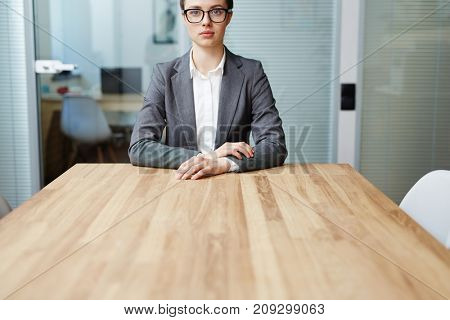 Confident businesswoman in formalwear looking at camera by table in office