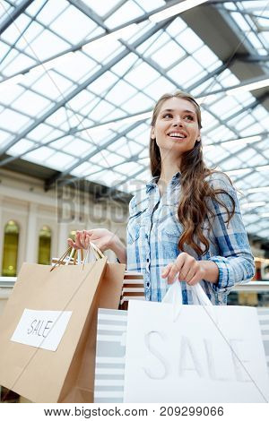 Young customer with paperbags walking down modern trade-center