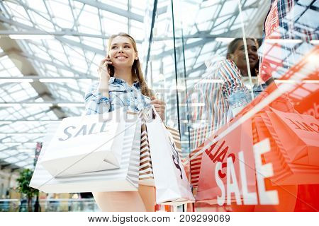 Happy buyer with bags talking by mobile phone by window display in the mall