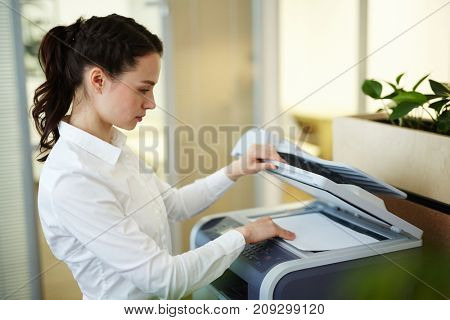 Young secretary making photocopies on xerox machine in office