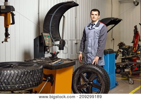 Professional car man installation of studded tires in auto repair service.