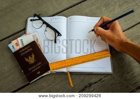 Thailand passport with money yellow ruler hand with pencil writing on notebook and glasses - concept prepare to travel.