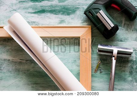 Tools for stretching a canvas print on stretcher bars. Canvas print, wooden stretcher bars, staple gun and plenty of staples, canvas pliers, fastener.
