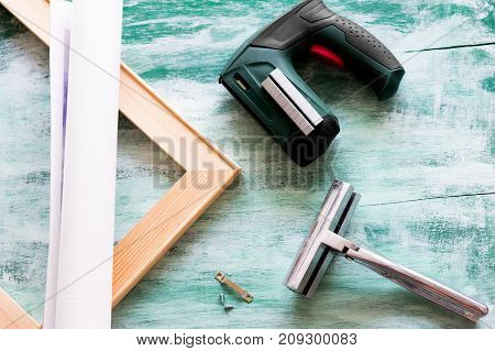 Tools for stretching a canvas print on stretcher bars. Canvas print, wooden stretcher bars, staple gun and plenty of staples, canvas pliers, fastener. Top view.